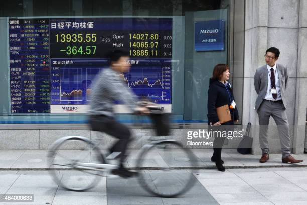 Pedestrians stand in front of an electronic stock board displaying a midday figure of the Nikkei 225 Stock Average as a man cycles past outside a...