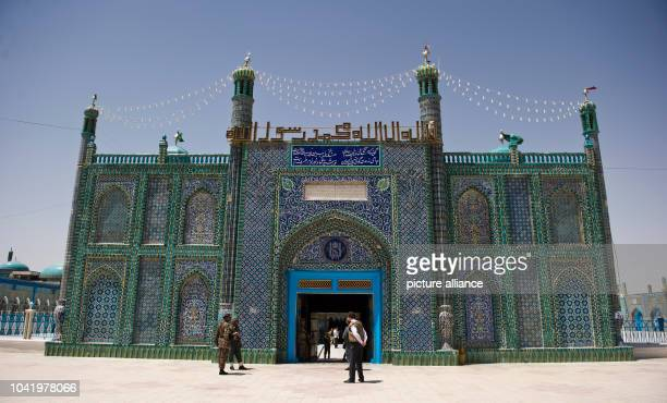 Pedestrians stand in front of the entrance to the Blue Mosque in MasariScharif Afghanistan 9 June 2013 Photo Nicolas Armer | usage worldwide