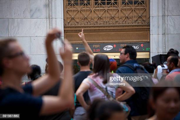 Pedestrians stand in front of the New York Stock Exchange in New York US on Friday Aug 19 2016 US stocks slipped for the first time in three days...
