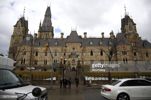Pedestrians stand in front of the West Block building of Parliament Hill the temporary home to the House of Commons in Ottawa Ontario Canada on...