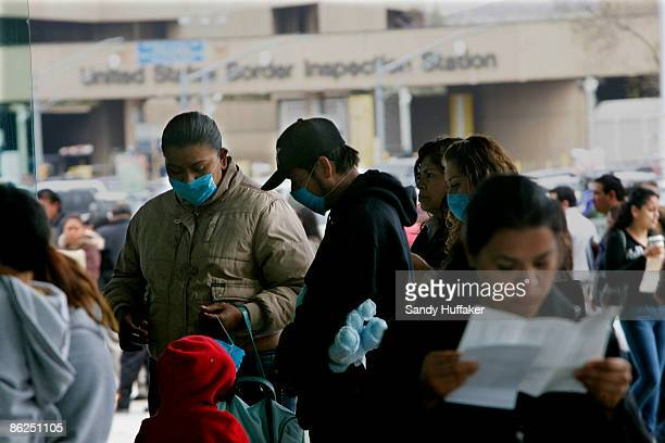 Pedestrians stand in line at the United States-Mexico border while wearing a surgical masks at the Port of Entry on April 27, 2009 in Tijuana,...