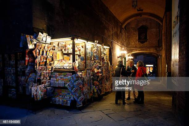 Pedestrians stand near a newspaper vendor's stall on a cobbled street in Siena Italy on Wednesday Jan 8 2014 Banca Monte dei Paschi di Siena SpA the...