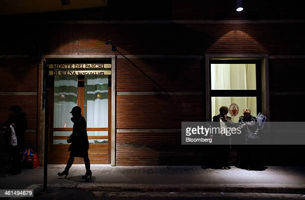 Pedestrians stand outside a Banca Monte dei Paschi di Siena SpA bank branch in Siena Italy on Wednesday Jan 8 2014 Monte Paschi the bailed out...