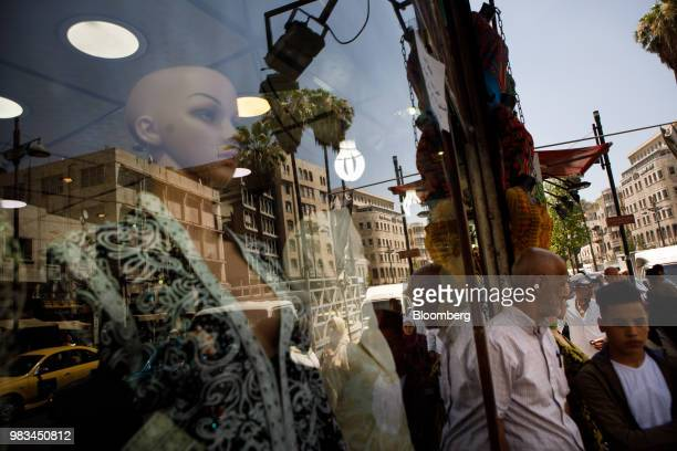 Pedestrians stand outside a women's fashion store in Amman Jordan on Thursday June 21 2018 President Trump and First Lady Melania Trump will host...