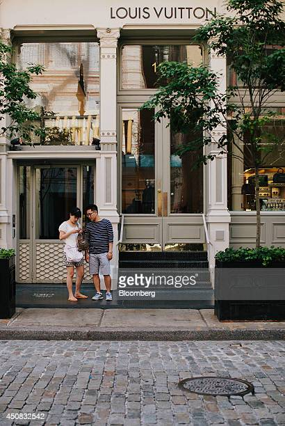Pedestrians stand outside of a LVMH Moet Hennessy Louis Vuitton SA store in the SoHo neighborhood of New York US on Wednesday June 18 2014 The...