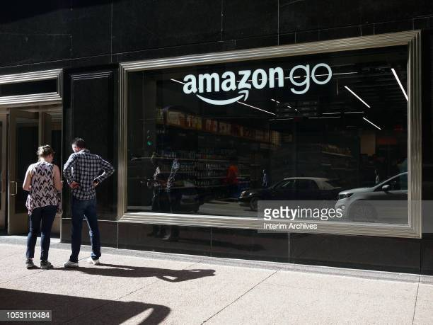 Pedestrians stand outside the window of the newly opened Amazon Go store located at 144 South Clark Street in Chicago Illinois October 2018