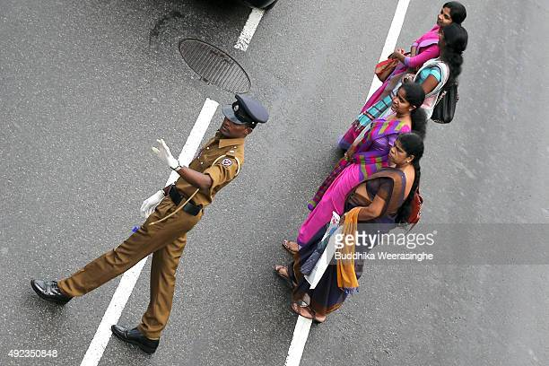 Pedestrians stand waiting to cross a road as a traffic policeman directs vehicles in a street on October 12 2015 in Colombo Sri Lanka The Sri Lankan...
