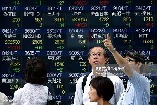 Pedestrians stand waiting to cross a road in front of an electronic stock board outside a securities firm in Tokyo Japan on Friday July 18 2014...