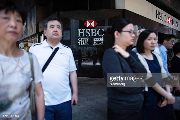 Pedestrians stand waiting to cross a road near an HSBC Holdings Plc bank branch in the Central district of Hong Kong China on Monday May 4 2015 HSBC...