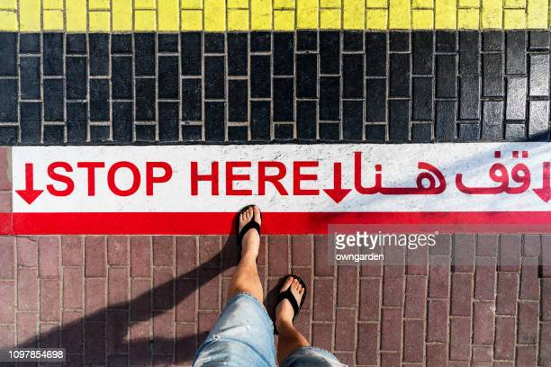 pedestrians standign in front of the stop line at the intersection - arab feet photos et images de collection