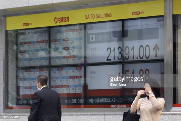 A pedestrians stands in front of an electronic stock board outside a securities firm in Tokyo Japan on Wednesday Oct 18 2017 As Prime Minister Shinzo...