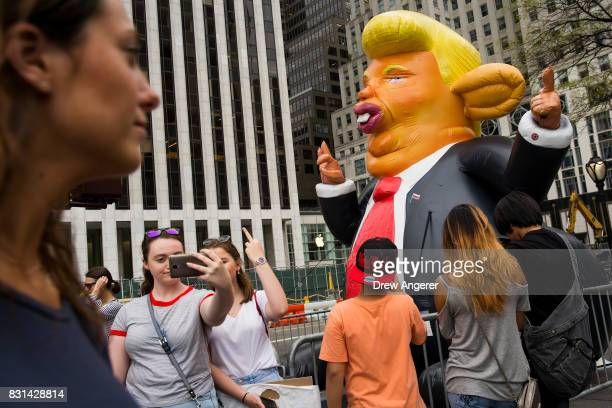 Pedestrians stop and take photos with a 15foot tall inflatable rat in the likeness of US President Donald Trump at the corner of Fifth Avenue and...