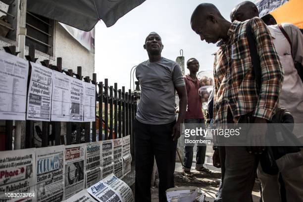 Pedestrians stop to browse the headlines displayed by a newspaper street vendor in Kinshasa Democratic Republic of the Congo on Friday Jan 11 2019...