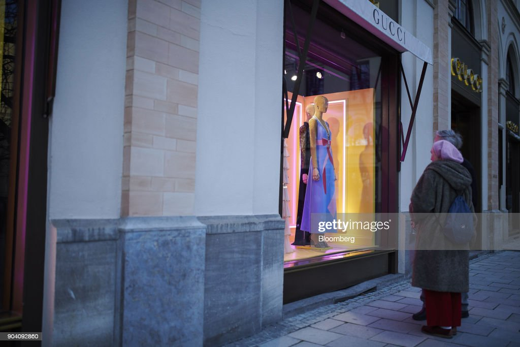 Pedestrians stop to browse womenswear in the window display of a Gucci luxury goods boutique, operated by Kering SA, in Munich, Germany, on Tuesday, Jan. 9, 2018. The German economy's solid 2017 performance extended into the final three months of the year, with growth of about half a percent. Photographer: Dominik Osswald/Bloomberg via Getty Images