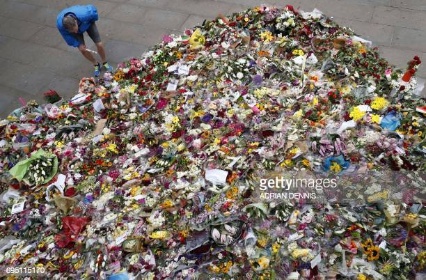 Pedestrians stop to look at floral tributes left by wellwishers on London Bridge in London on June 12 following the June 3 terror attack that...