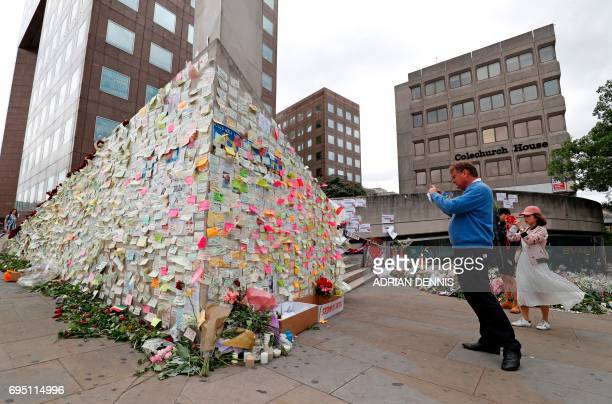 Pedestrians stop to look at messages left by wellwishers on London Bridge in London on June 12 following the June 3 terror attack that targeted...