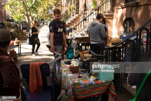 Pedestrians stop to look at various items displayed in a stoop sale in the Cobble Hill neighborhood of Brooklyn New York October 21 2017