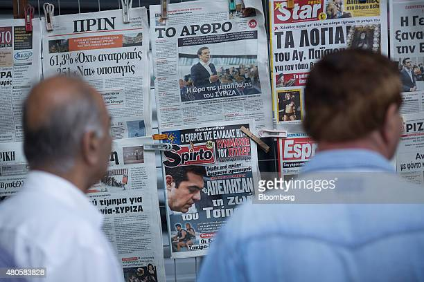 Pedestrians stop to read newspaper front pages outside a magazine kiosk in Athens Greece on Monday July 13 2015 Greece has been in financial limbo...