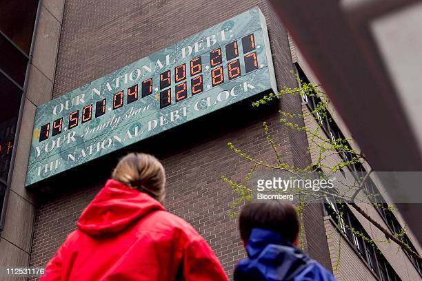 Pedestrians stop to view the National Debt Clock in New York US on Tuesday April 19 2011 US President Barack Obama said today at a town hall meeting...