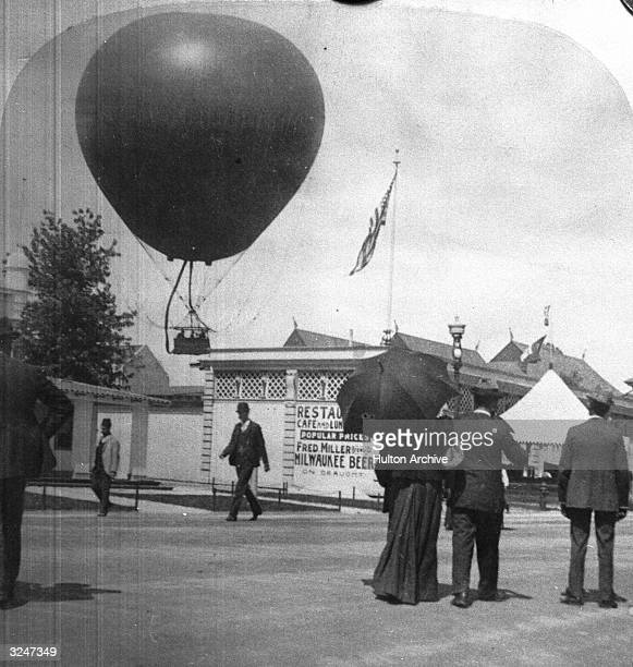 Pedestrians stop to watch a balloon rising over buildings at the Midway Plaisance World's Fair Chicago Illinois