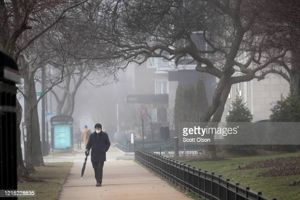 Pedestrians stroll along Lake Shore Drive across the Lake Michigan on March 27, 2020 in Chicago, Illinois. Upset by residents continuing to gather at...