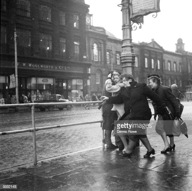 Pedestrians struggle against strong winds at Britain's windiest spot, on Edinburgh's Princes Street opposite the Waverley Steps, which funnel wind up...