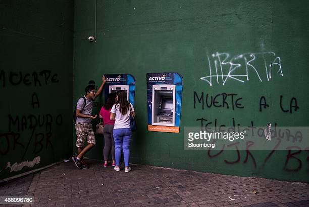 Pedestrians take out money at an automated teller machine next to graffiti that reads 'Death to the Televised Dictatorship' referencing Venezuelan...