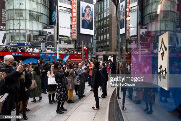 Pedestrians take photographs of a calligraphy work showing the name of Japan's next imperial era 'Reiwa' displayed in the Ginza district on April 01...