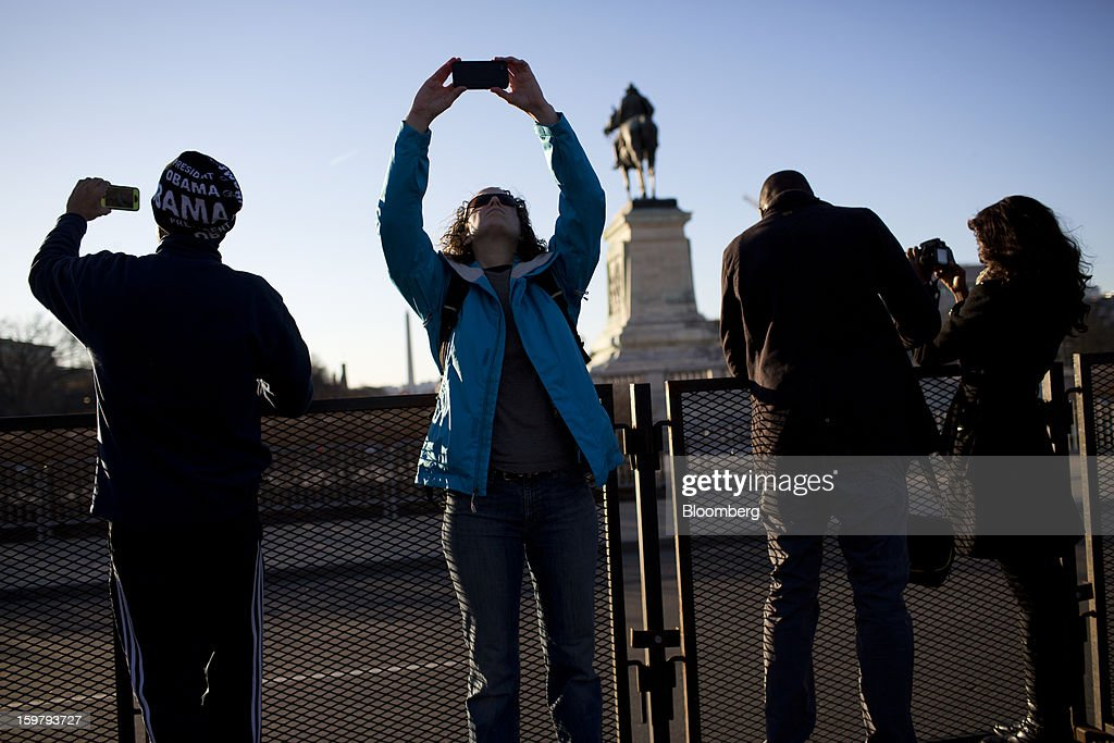 Pedestrians take photos ahead of the presidential inauguration in Washington, D.C., U.S., on Sunday, Jan. 20, 2013. As he enters his second term U.S. President Barack Obama has shed the aura of a hopeful consensus builder determined to break partisan gridlock and adopted a more confrontational stance with Republicans. Photographer: Victor J. Blue/Bloomberg via Getty Images