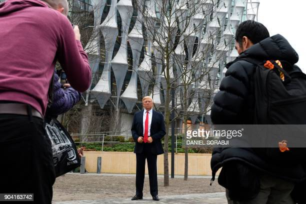 Pedestrians take pictures of a Madame Tussauds wax figure of US President Donald Trump outside the new US Embassy in Embassy Gardens in southwest...