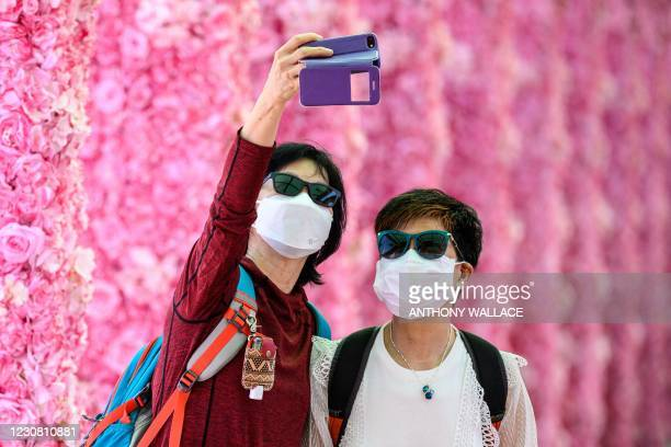 Pedestrians take selfies in a floral themed passageway in Hong Kong on January 27, 2021.