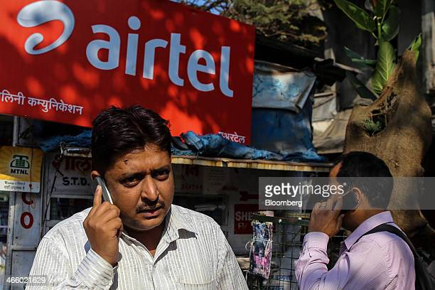Pedestrians talk on their mobile phones in front of a store displaying a Bharti Airtel Ltd advertisement in Mumbai India on Wednesday Jan 29 2014 The...