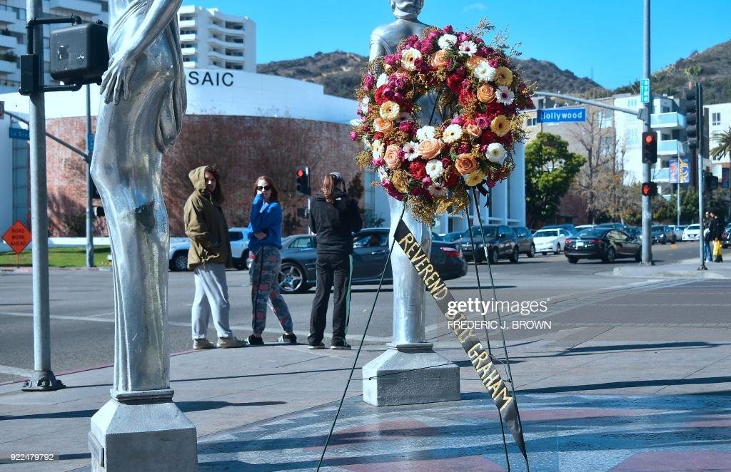Pedestrians turn back to look at the wreath of flowers on display, courtesy of the Hollywood Chamber of Commerce, in tribute to the late Evangelist Pastor Billy Graham in Hollywood, California on February 21, 2018. Graham, the influential Southern preacher who became a spiritual advisor to several US presidents and millions of Americans via their television sets, died Wednesday. He was 99. / AFP PHOTO / Frederic J. BROWN