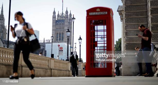 Pedestrians us their mobile phones as they walk along Whitehall, near the Houses of Parliament in Westminster, central London on July 2, 2019. -...