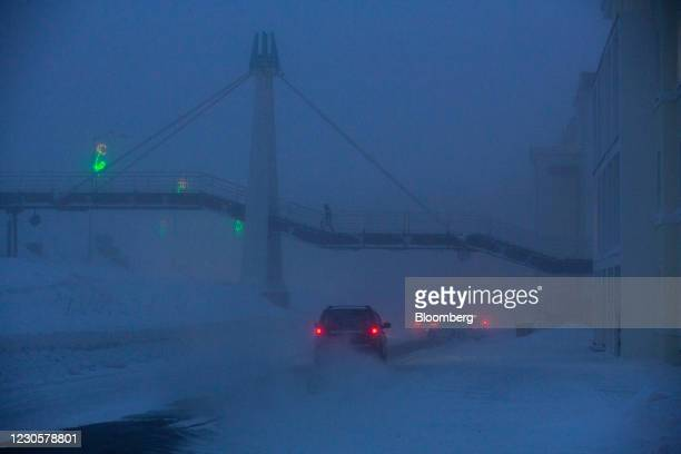 Pedestrians use a footbridge over a road in near-darkness in Norilsk, Russia, on Monday, Dec. 21, 2020. Norilsk may soon be famous for a different...