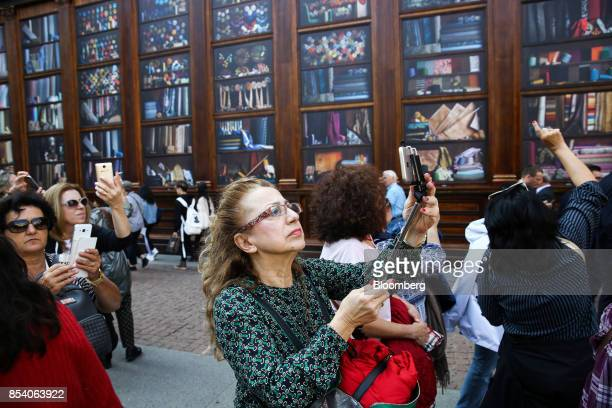 Pedestrians use smartphones to take selfie photographs in central Milan Italy on Monday Sept 25 2017 The Italian government sees the country's debt...