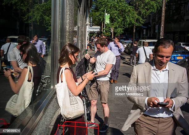 Pedestrians use their hand held devices near a subway stop in the Brooklyn borough of New York
