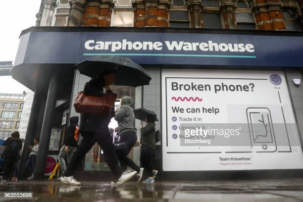 Pedestrians use umbrellas to shelter from the rain as the pass a Carphone Warehouse retail store operated by DixonsCarphonePlc in central London UK...