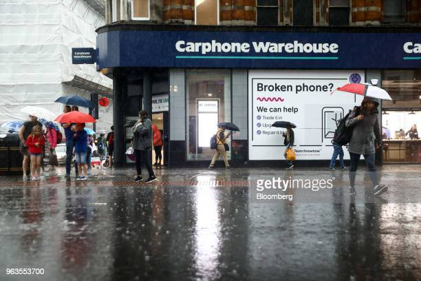 Pedestrians use umbrellas to shelter from the rain as they pass a Carphone Warehouse retail store operated by DixonsCarphonePlc in central London...