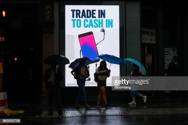 Pedestrians use umbrellas to shelter from the rain as they stand in front of a digital advertising display in front of a Carphone Warehouse retail...