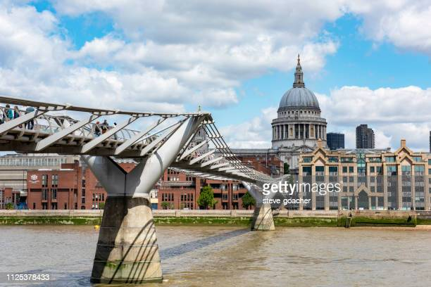 pedestrians using the london millennium footbridge to cross the rive thames between the city of london and bankside. - greater london stock pictures, royalty-free photos & images