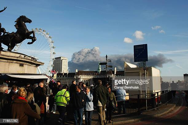 Pedestrians view a large plume of thick black smoke visible across the whole of the London skyline beyond the skyline of County Hall and the London...