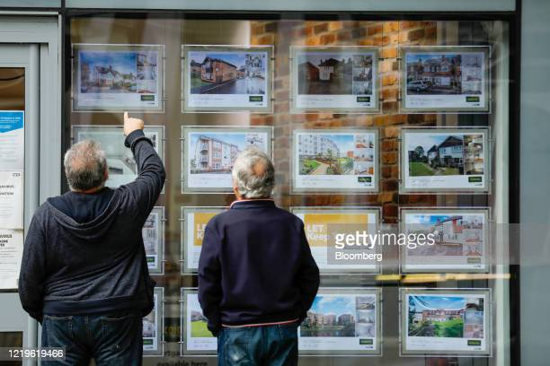 Pedestrians view displays in an estate agent's window in Guildford, U.K., on Friday, June 12, 2020. U.K.House pricesfell the most in more than a...