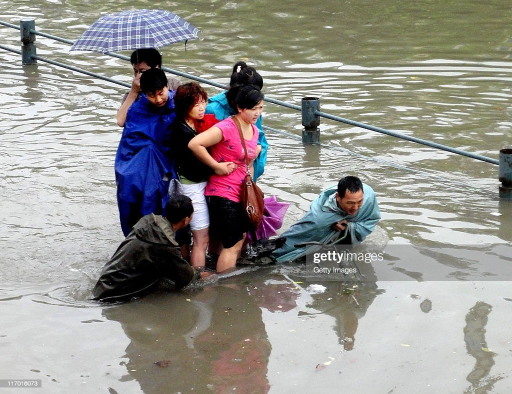 Pedestrians wade in a flooded street after heavy rainfall on June 18, 2011 in Wuhan, Hubei Province of China. A heavy rainstorm hit Wuhan on Saturday, causing flooding across the region.