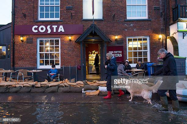 Pedestrians wade through flood water as sandbags sit outside a Costa Coffee shop operated by Whitbread Plc on the high street in Datchet UK on...