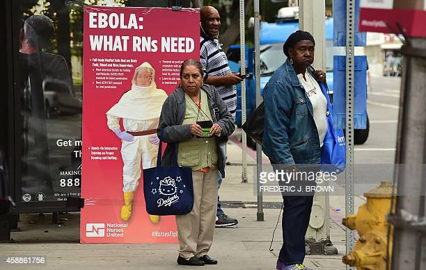 Pedestrians wait at a bus stop beside an Ebola awareness poster ahead of a lunch hour rally by nurses drawing attention to properly equipping and...