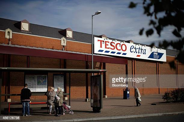 Pedestrians wait at a bus stop outside a Tesco Extra supermarket store operated by Tesco Plc in the Surrey Quays district of London UK on Thursday...