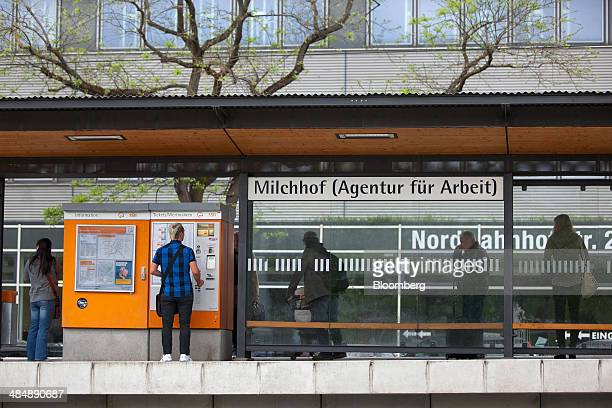 Pedestrians wait for transportation at a tram stop outside a Agentur fuer Arbeit employment office in Stuttgart Germany on Monday April 14 2014...