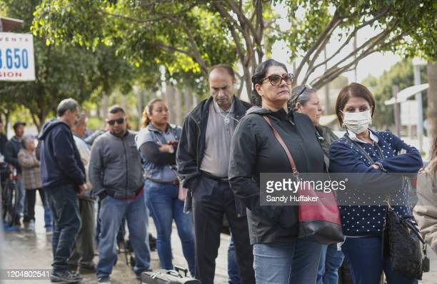 Pedestrians wait in line to cross the border on March 2, 2020 in Tijuana, Mexico. A federal appeals court on Friday blocked a Trump administration...