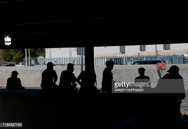 Pedestrians wait near the border crossing in Mexicali, Mexico at the Port of Entry to the United States on April 1, 2019. - US President Donald Trump...